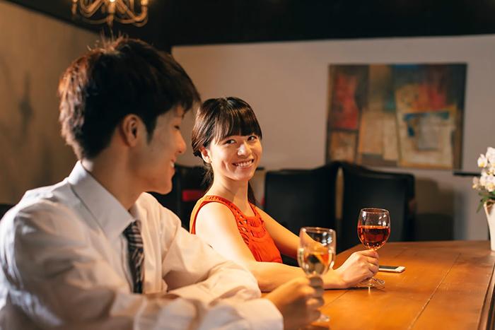 カウンターでお酒を飲むカップル
